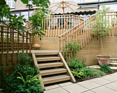 STEPS LEAD From PAVED AREA ONTO WOODEN DECK AND HIGHER DECK with TABLE AND CHAIRS. Designer: Sarah LAYTON