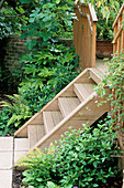 WOODEN STEPS LEAD From PAVED AREA ONTO DECKED TERRACE IN A Garden DESIGNED by Sarah LAYTON