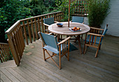 TABLE AND CHAIRS On A DECKED TERRACE IN A Garden DESIGNED by Sarah LAYTON