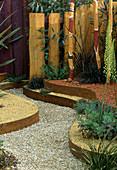 Farbiger Kies auf unterschiedlichen Ebenen, Ophiopogon, Eucalyptus, Sedum, Zäune und Stäbe in lebhaften Farben gestrichen