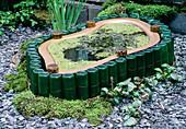 Kleiner Teich in Plastikwanne, eingefaßt mit grünen Glasflaschen und schwarzem Schiefer-Mulch , Wasserlinsen und Zwerg-Seerose
