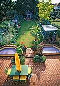 VIEW OVER THE NICHOLS Garden with TERRACOTTA Patio, Green TABLE AND CHAIRS, Orange Sun SHADE, TRACHYCARPUS FORTUNEI, Greenhouse, GAZEBO AND LILAC DECKED SANDPIT & Pool