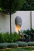 'Gesichts-'Skulptur neben Santolina von Strahler beleuchtet