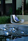 Schwarzes Wasser, Metallkugeln, Holzabdeckung, Sessel mit Kissen, Holzdeck und Gräser , Hampton Court