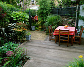 SMALL Town Garden with DECKING, PAVING, TABLE AND CHAIRS, TRACHYCARPUS FORTUNEI AND HAMMOCK. Designer: Sarah LAYTON