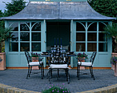 HOUSE BEAUTIFUL Garden, HAMPTON Court 2003: Designer DAVID DOMONEY. SUMMERHOUSE with ARCH SHAPED Patio AND TABLE AND CHAIRS
