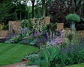 Halbrundes Beet vor Gartenmauer : Delphinium (Rittersporn), Campanula (Glockenblumen), Anchusa (Ochsenzunge), Iris barbata (Schwertlilie), Nepeta (Katzenminze), weiße Rosa (Ramblerrosen)
