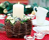 Kerzendeko mit Tannenzapfen: Tontopf mit Tannenzapfen und Früchten dekoriert