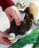 Kerzendeko mit Tannenzapfen: 2. Step. Tannenzapfen mit Golddraht um den Tontopf