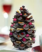 Gefüllter Weihnachtszapfen. Zapfen mit diversen weihnachtlichen Material gefüllt