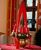 Hängender Adventskranz mit Bändern und roten Kerzen