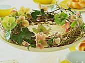 Kranz aus Weidenzweigen dekoriert mit Blüten der Lenzrose
