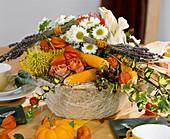 Korb mit Gesteck aus Rosen, Maiskolben, Herbstchrysanthemen, Lampionblume