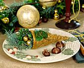 Tellerdeko mit goldbesprühter Kokostüte, Efeublatt als Namensschild