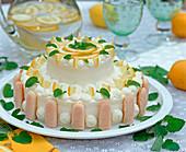Torte dekoriert mit Zitronenstückchen und Zitronenmelisse