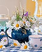 Milchkanne mit Strauß aus Margeriten, Glockenblumen und Gräsern