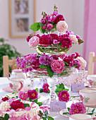 Tischdekoration mit Etagere aus Glasschalen gefüllt mit Rosenblüten