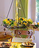 Hängende Tischdeko: Metallgestell mit kleinen Sträußchen aus