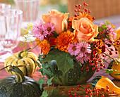 Cucurbita / grüner Kürbis als Vase mit Gesteck aus Rosa 'Versilia' / Rosen u. Ha