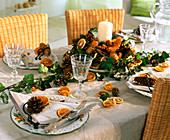 Tischdeko mit Orangenscheiben, Kiefernzapfen, Efeuranken, Fichtenzapfen