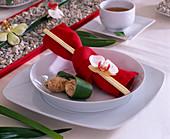 Tellerdeko asiatisch: Rote Serviette mit Stäbchen und Phalaenopsis