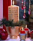 Adventliches Gesteck mit selbstbeschrifteter Kerze in Goldvase und Kiefernzweige