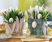 Weizengras mit Eiern und Federn in Rupfentasche und Sisalkörbchen