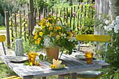 Gelber Sommerstrauss auf Tisch im Garten