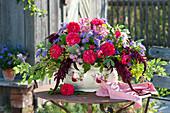 Laendliches Gesteck in Jardiniere mit Rosendekor