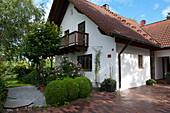 Laendliches Anwesen mit gepflasterter Einfahrt, Buxus