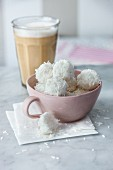 Vegan coconut balls with birch sugar next to a latte macchiato