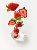 Strawberries falling into milk