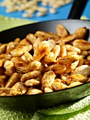 Crunchy sugar coated almonds in a pan