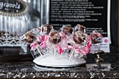 Vegan cake pops gift-wrapped in transparent cellophane and displayed on a stand