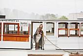 Blonde Frau in bordeauxroter Schluppenbluse, Rock in Wickeloptik, Tuch und Stiefeletten auf einem Boot