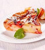 Ein Stück Obstkuchen mit Puderzucker und Minze