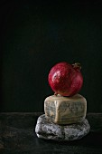 A whole pomegranate on decorative stones against a black background