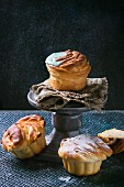 Homemade cruffins (a cross between a croissant and a muffin) with icing on a grey cake stand