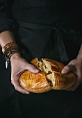 Homemade traditional armenian sweet cake gata in female hands over black background