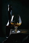 Bottle and glass of french apple calvados, standing on black tablecloth over balck background
