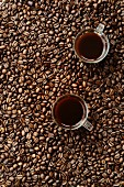 Coffee beans and two cups of coffee in glass cups