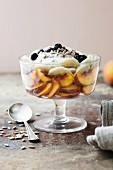 Healthy layered trifle – coconut yoghurt, sliced banana, peach, topped with sunflower seeds and blueberries