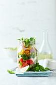 Cherry tomato salad with corn salad and mozzarella in a jar