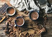 Heiße Schokolade mit Zimt in zwei Bechern, Anis, Nüsse und Kakaopulver auf rustikalem Holzuntergrund