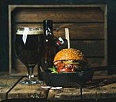 Homemade beef burger with crispy bacon, fresh vegetables and ketchup in black cast iron pan, with glass of dark beer