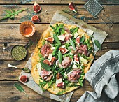 Fig, prosciutto, rocket and sage flatbread pizza with a glass of rosé wine