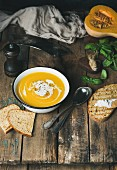 Creamy pumpkin soup in a white bowl with fresh basil and grilled bread slices on a rustic wooden table