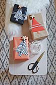 Verpackte Geschenke mit Tannenbäumchen aus Papier