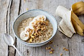 Rice porridge made with lupin and coconut milk with banana and crunchy flakes