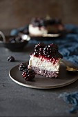 A piece of cheesecake with blackberries